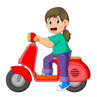 女の子が赤いスクーターでポーズをとっています。
