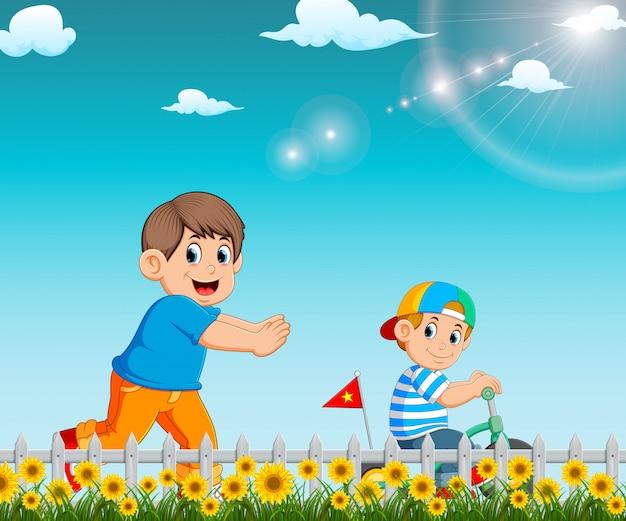 Мальчик бежит к брату, который катается на велосипеде в саду