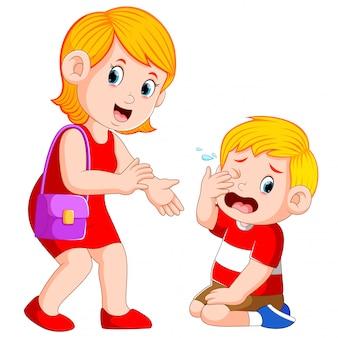 母親は泣いている男の子を落ち着かせようとしています