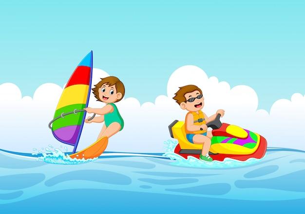 男の子と女の子はジェットスキーとセーリングボートで遊んでいます。