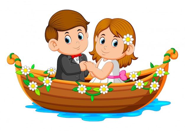 カップルはそれの周りの花と美しいボートに乗ってポーズをとっています。