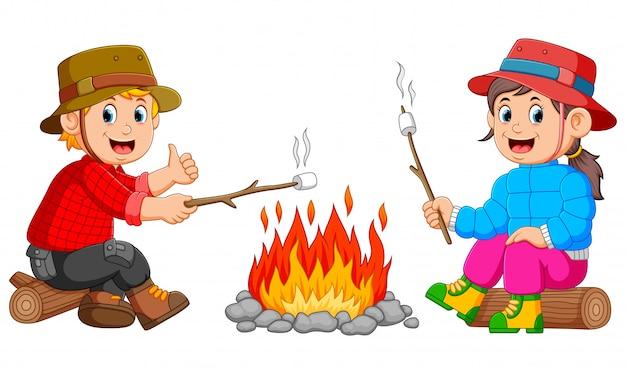 子供たちはキャンプでマシュマロを燃やしています