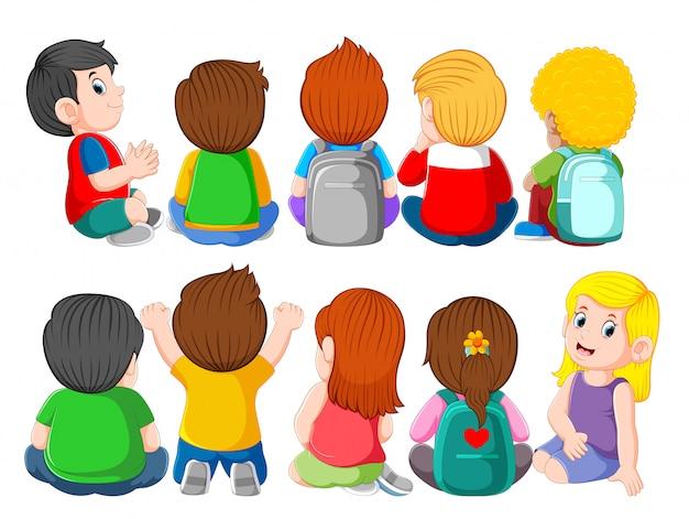座っているかわいい子供たちのグループの背面図