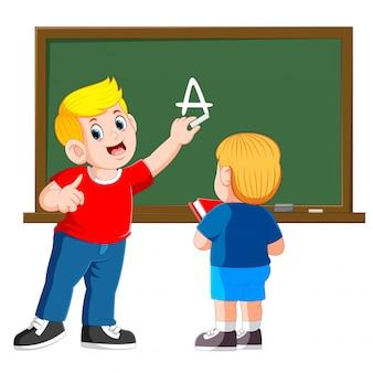 父は背景に黒板と幼い息子を教えています