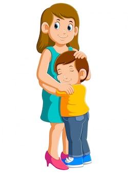 若い母親と彼女の魅力的な幼い息子はハグと笑顔
