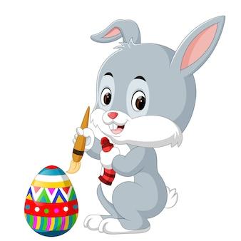かわいいイースターバニー、卵を描く