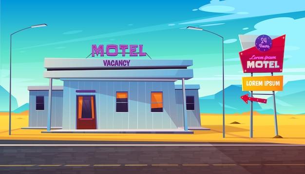 Небольшое круглосуточное здание мотеля с освещенным дорожным знаком возле шоссе