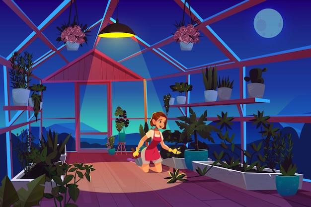 夜の庭の植物の世話で温室の女性。
