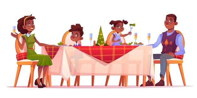 クリスマスディナーの幸せな家族がお祝いテーブルに座る