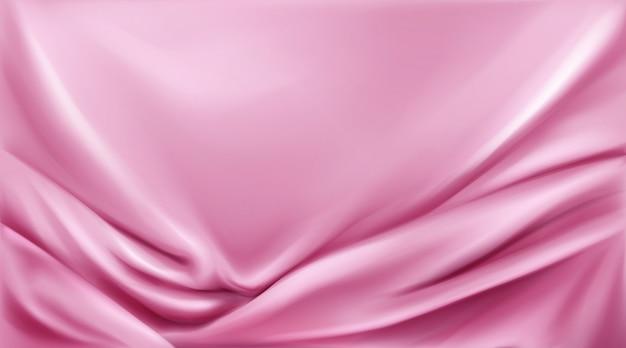 ピンクのシルクの折り畳まれた生地背景豪華な布
