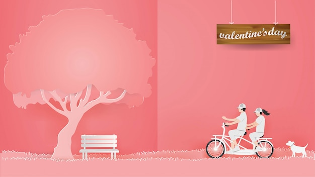 ピンクの背景の赤い芝生の上の自転車に乗るカップル