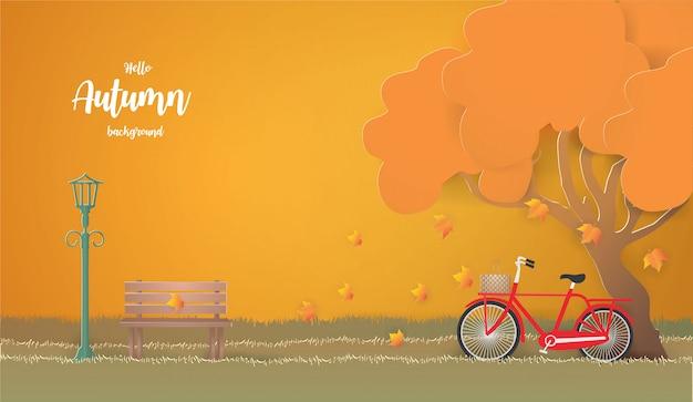 秋の図の木の下で赤い自転車。