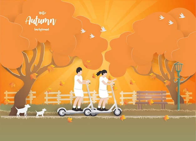 秋のバックグラウンドで電動スクーターに乗るカップル。