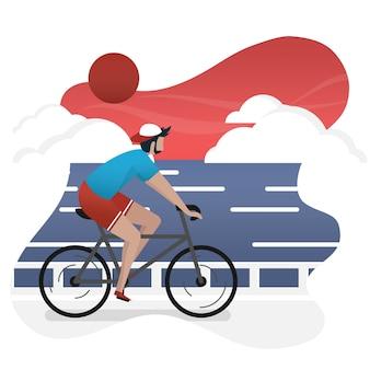 男は日没時に海の風景と自転車に乗っています。自由時間に自転車に乗る男