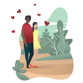 カップルの恋人の男と女が緑豊かな公園を歩いています。バレンタインおめでとう