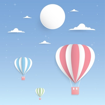空と月の紙アートのカラフルな風船