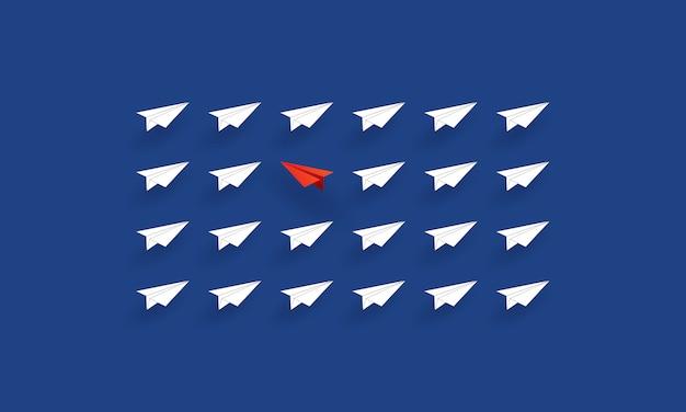 別の方向に飛んでいる赤い紙飛行機