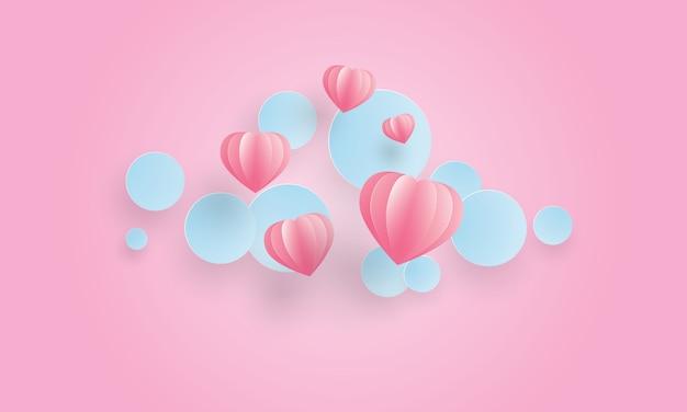 ピンクのハート形と浮かぶ青い円のペーパーアート、バレンタインデー
