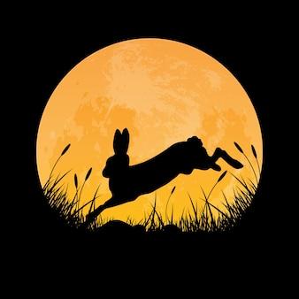 草原の上を飛ぶウサギのシルエット