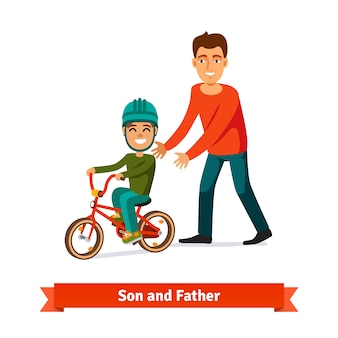 Отец учит сына кататься на велосипеде