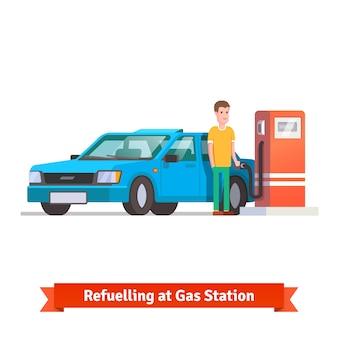 ガソリンスタンドで彼の車に給油する男