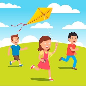 草原で凧を一緒に遊んでいる子供たち