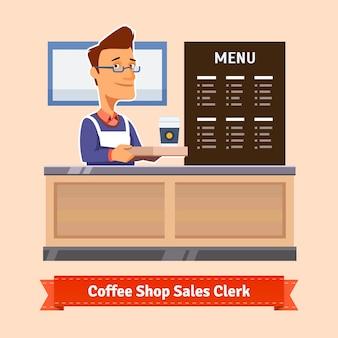 若い店のアシスタントは、コーヒーのカップを提供
