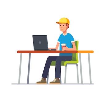 Молодой человек в шапке, работающий на своем чистом офисном столе