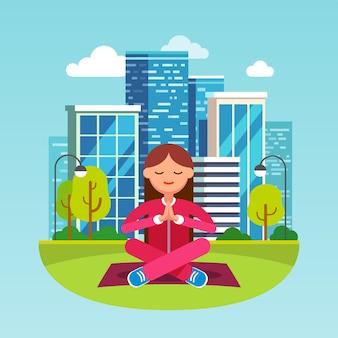 Молодая женщина, медитируя в большом городском парке