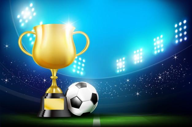 Золотые кубки и футбольный мяч на стадионе
