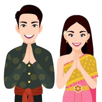 タイの男性と女性の伝統的な衣装、「サワディー」と白い背景の漫画のキャラクターにタイの旗を挨拶タイの人々
