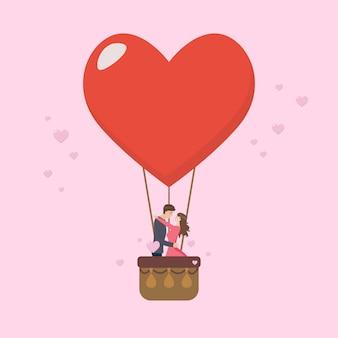 愛情のあるカップルが大きなハートのバルーンにキスします。