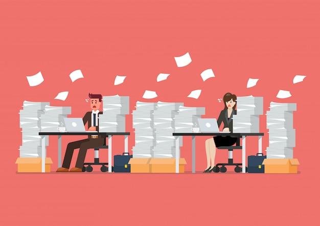 忙しい過労の男性と女性のラップトップとオフィスで書類の山のテーブルに座って