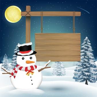 夜の冬の丘に木製ボードサインと雪だるま