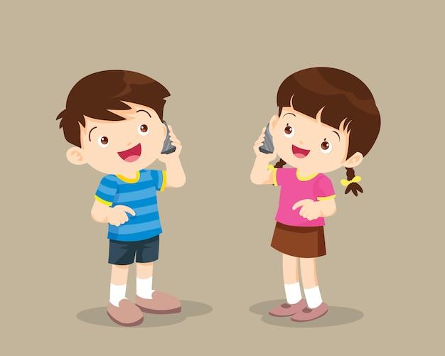 Мальчик и девочка разговаривают по мобильному телефону