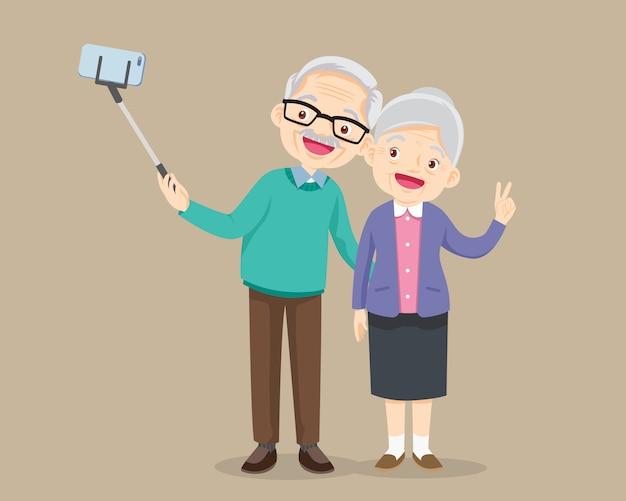 高齢者のカップルがスマートフォンで自分撮り写真を作る