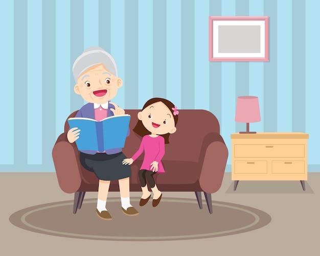 本とソファの上に孫と座っている祖母