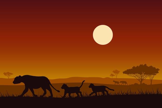 アフリカの野生生物シルエットの雌のライオンと赤ちゃんのライオン。