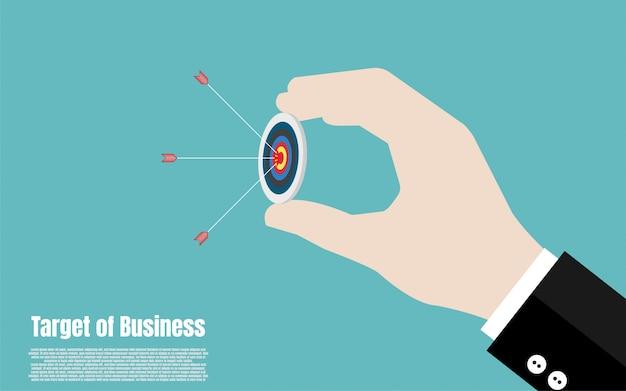 ビジネスマンの手は矢印でターゲットを保持します