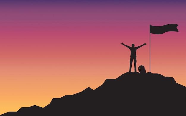 Силуэт счастливый человек, поднимая руку, стоя на вершине горы