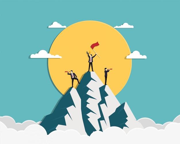 赤い旗と金のトロフィーを保持しているチームのビジネスマンが山の上に立つ