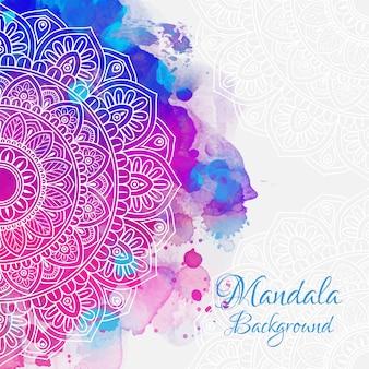 白い手は水彩の背景にマンダラを描く。
