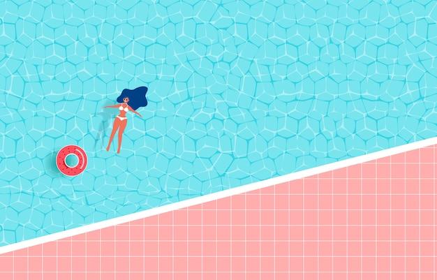 女の子とゴム製のリングが付いている夏のプール。