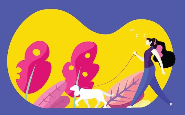 若い女性が公園で犬を散歩