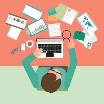 彼の机の上で懸命に働く忙しい実業家