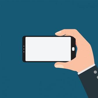 Бизнесмен, держа смартфон на синем фоне.