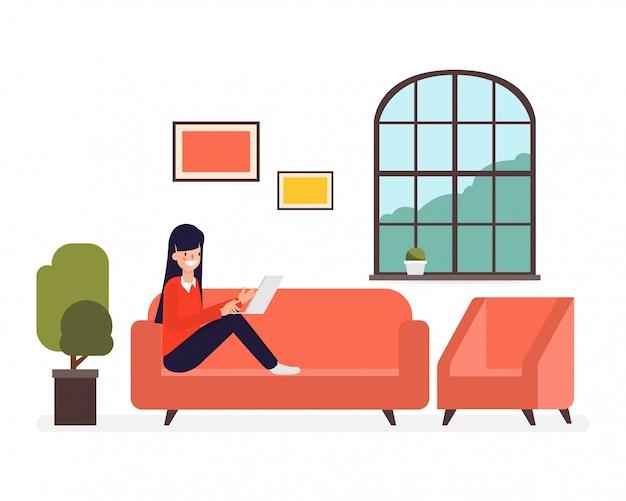 フリーランスの女性がソファで仕事し、仕事はラップトップでやっています。