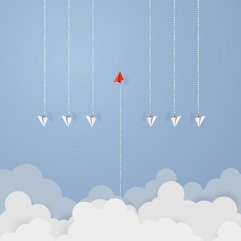 ビジネスの青い空を飛んでいる赤い紙リーダー飛行機