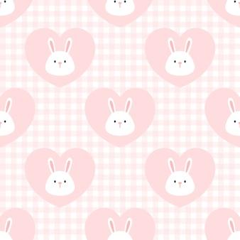 心のシームレスなパターンバックグラウンドでかわいいウサギ