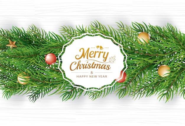 白い木の上にモミの枝とクリスマスの挨拶カード